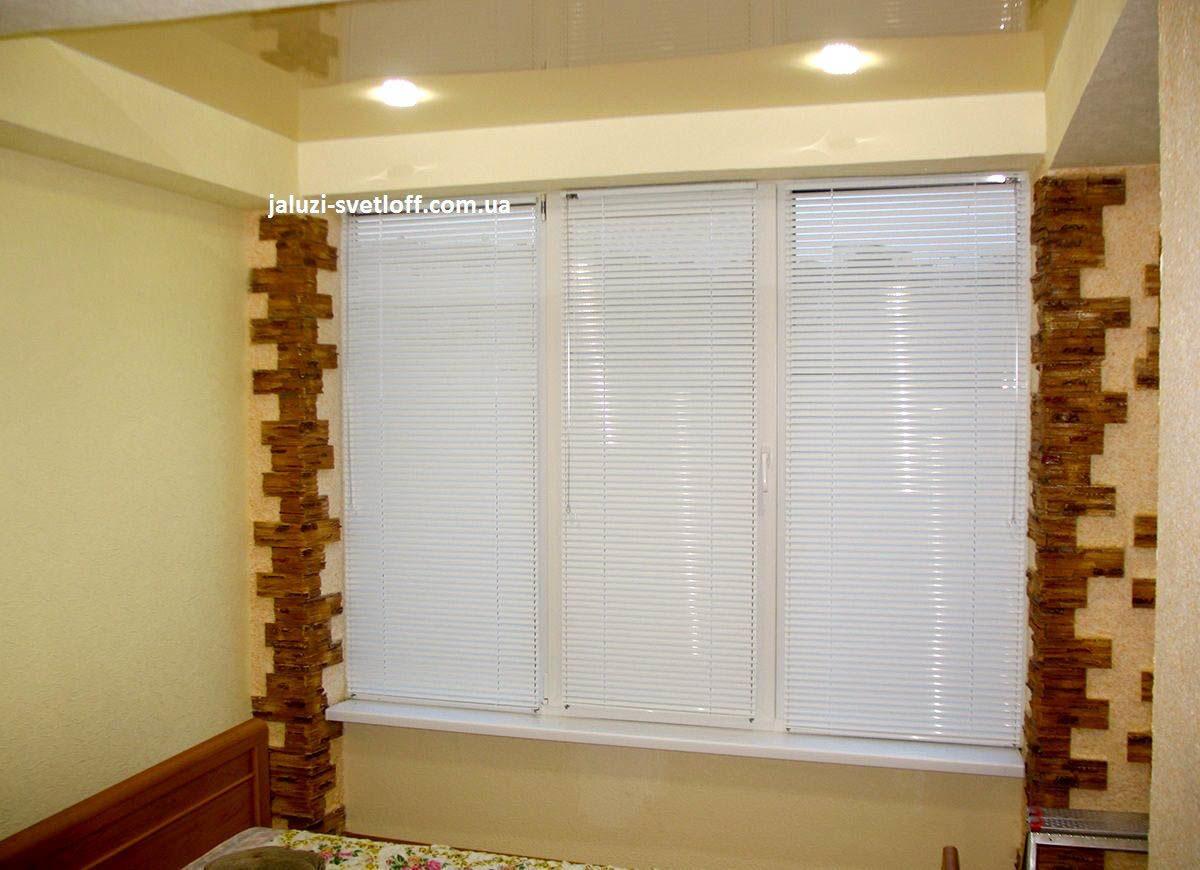 белые горизонтальные жалюзи на окнах с деревяными вставками на откосах