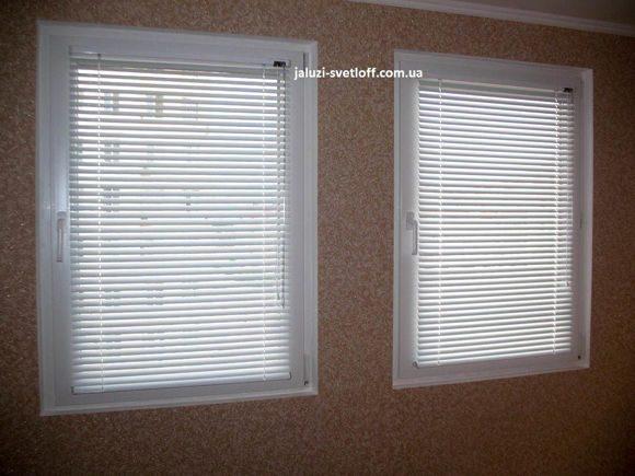 белые стандартные горизонтальные жалюзи на двух соседних окнах