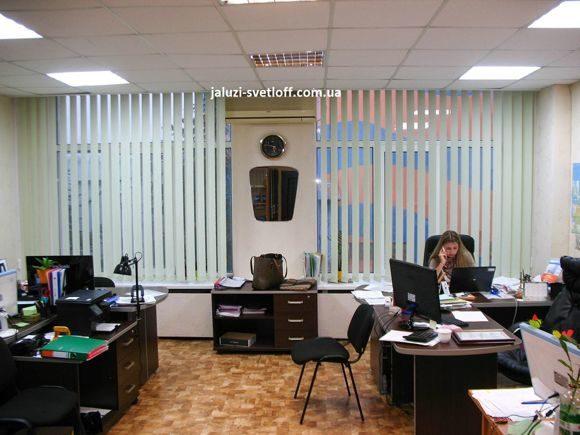 белые вертикальные жалюзи на офисных окнах