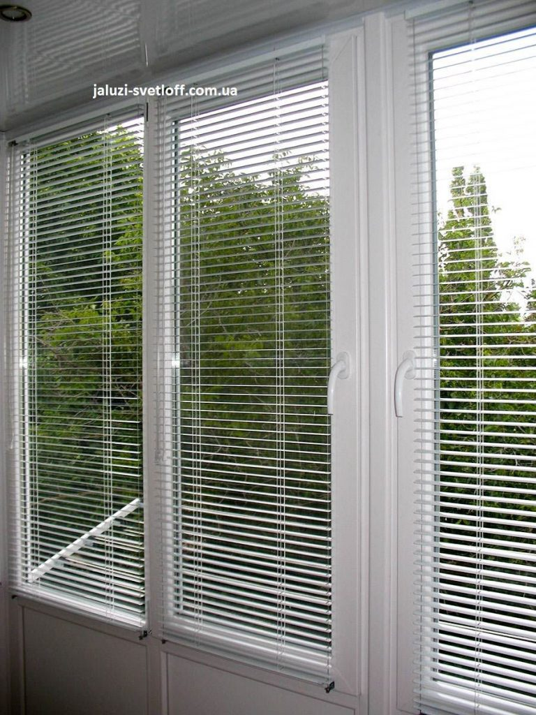 Белые жалюзи на окнах балкона