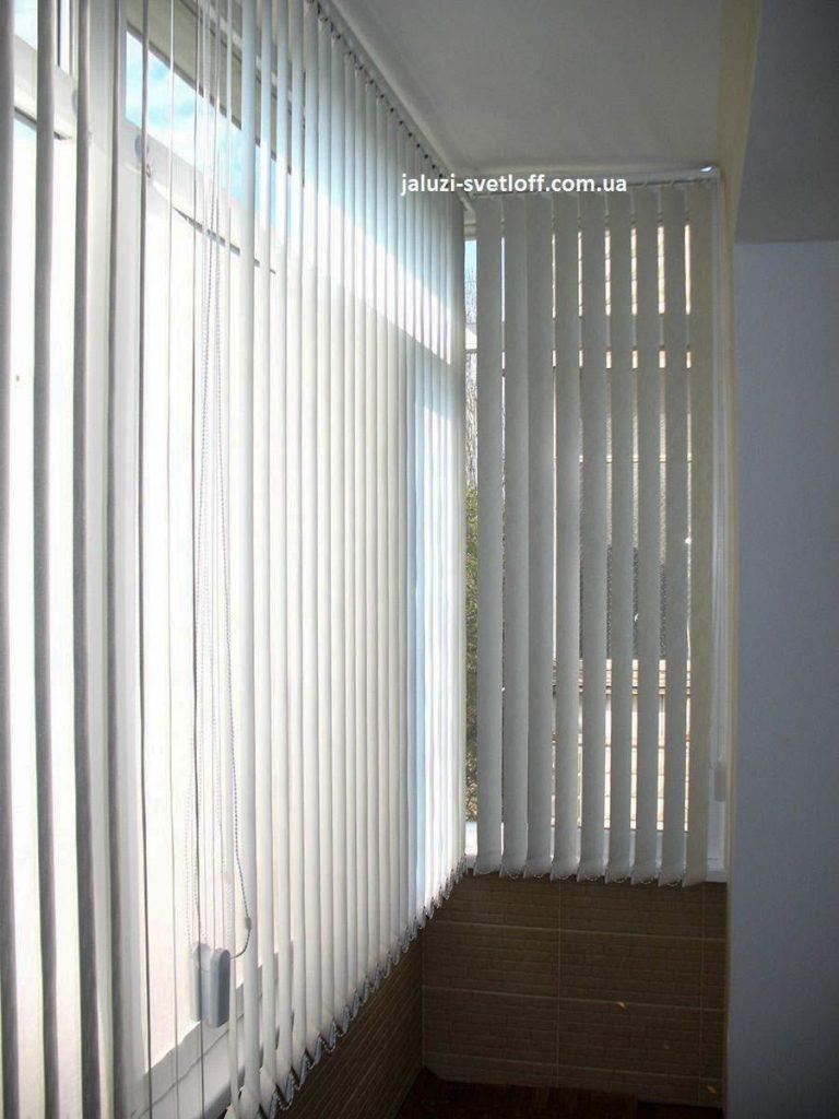 Белые вертикальные жалюзи на окнах лоджии
