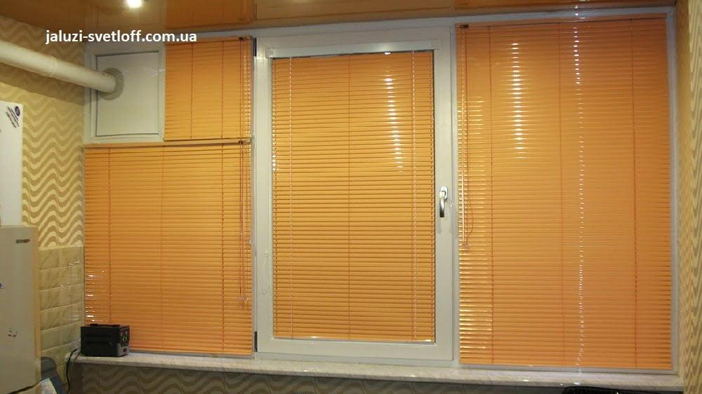 Горизонтальные жалюзи светло-оранжевого цвета на кухонном окне