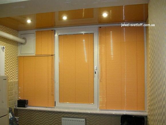 Горизонтальные жалюзи оранжевого цвета на створках кухонного окна