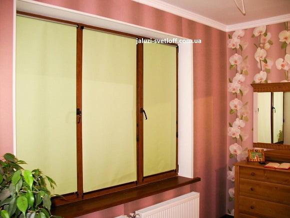Рулонные шторы открытого типа на окне спальни